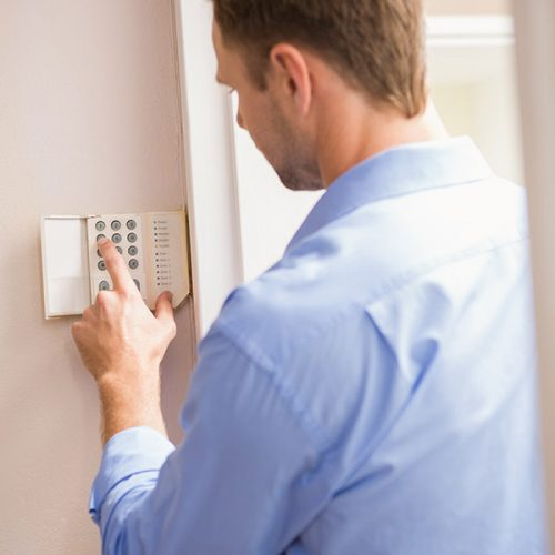 man-arming-a-home-alarm-on-the-wall-P23QL34-70